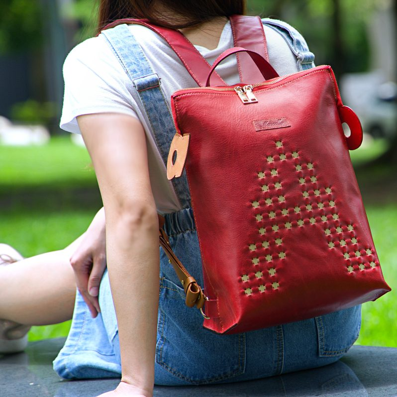 red backpack purse model sitting mobile